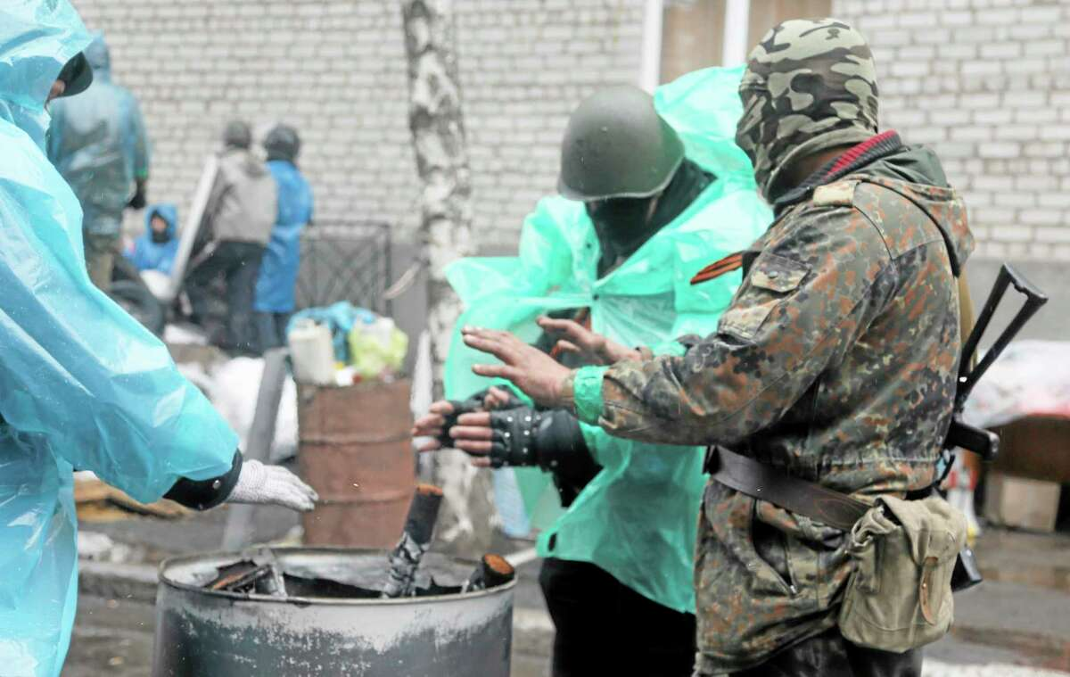 Pro-Russian gunmen warm themselves next to a bonfire as they guard a seized police station in the eastern Ukraine town of Slovyansk on April 13. (AP PHOTO/EFREM LUKATSKY)