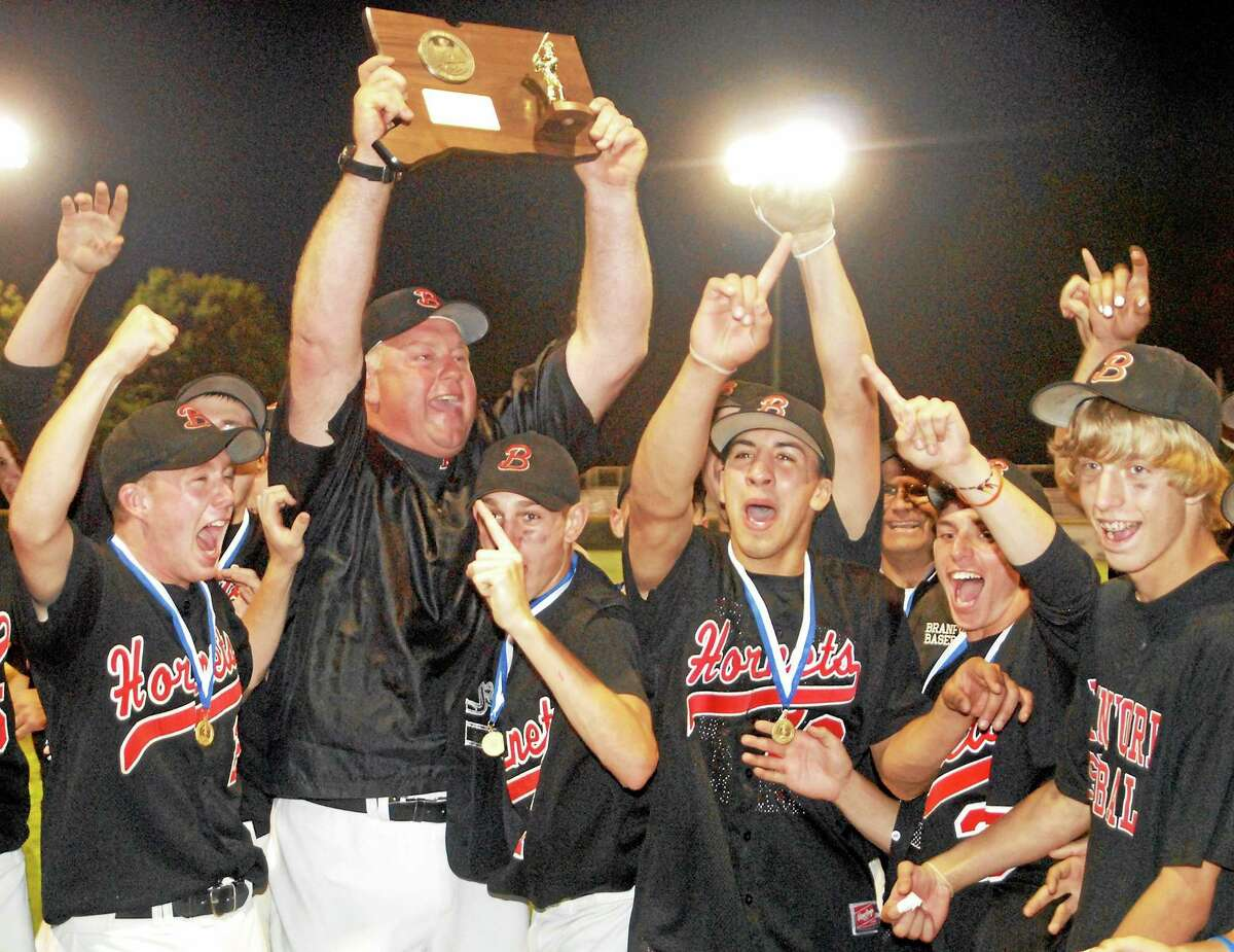 """Branford baseball coach George Dummar raises the Class L state championship plaque after the Hornets defeated Berlin for the title in 2009. Dummar succumbed to cancer last Sunday. As Register sports columnist Chip Malafronte points out, Dummar was the link to 100 years of Branford baseball history. Frank """"Beauty"""" McGowan debuted with the Branford High varsity team in 1914. When McGowan was 79, he was a scout with the Orioles and signed Dummar in 1980. Dummar eventually coached Mike Olt, who clubbed 12 homers as a rookie this year for the Chicago Cubs."""
