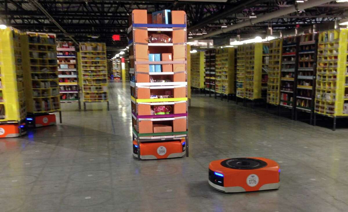 A Kiva robot drive unit is seen, foreground, before it moves under a stack of merchandise pods, seen on a tour of one of Amazon's newest distribution centers in Tracy, Calif., Sunday.