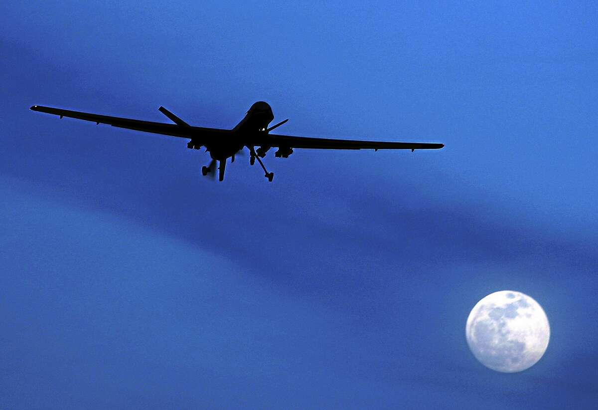 In this Jan. 31, 2010, photo, an unmanned U.S. Predator drone flies over Kandahar Air Field, southern Afghanistan, on a moon-lit night.
