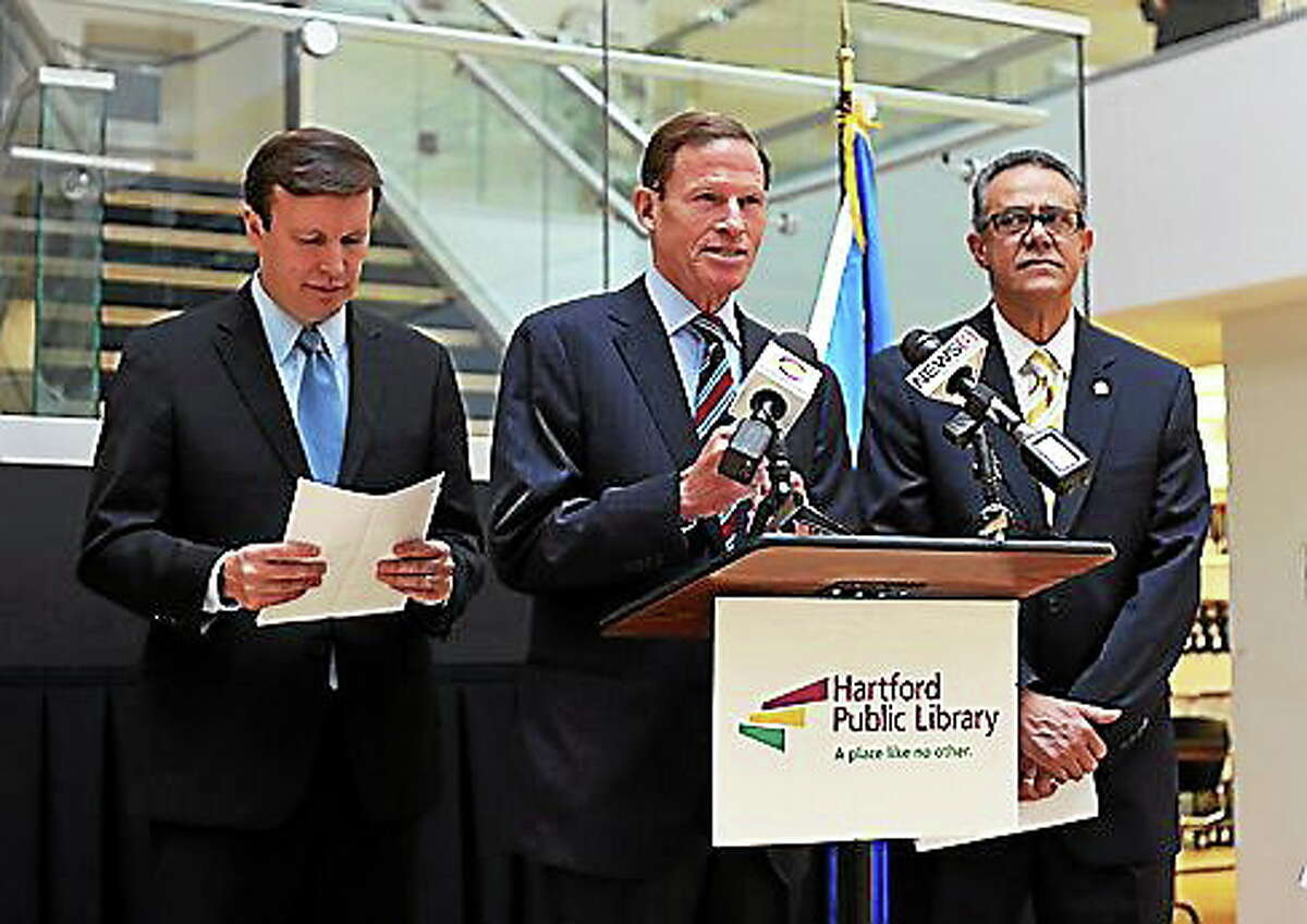 U.S. Sens. Chris Murphy, left, and Richard Blumenthal speak at a press conference Monday. Galo Rodriguez, president and CEO of the Village for Families and Children, is at right.