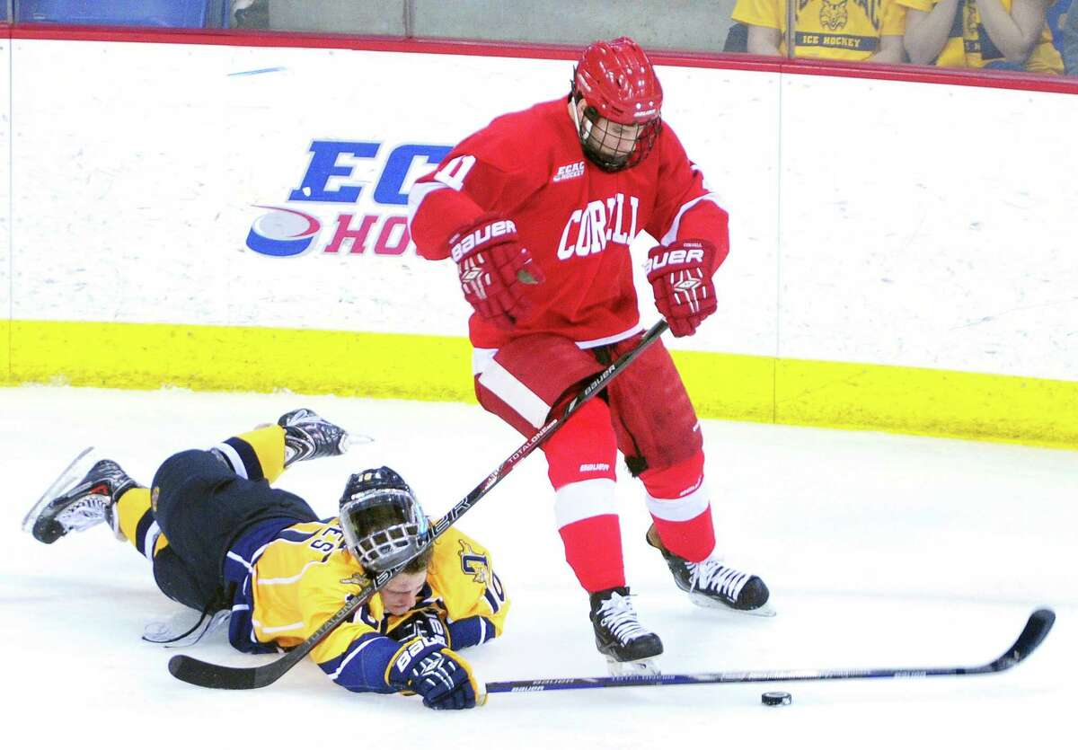 Quinnipiac's Connor Jones, left, hits the ice while battling for the puck with Cornell's Eric Freschi in Friday's game. Cornell won 2-1.