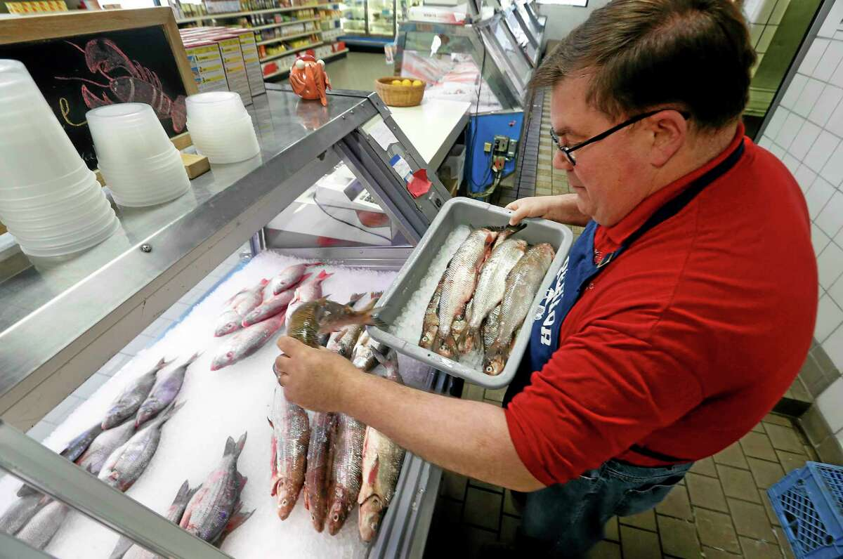 Kevin Dean, co-owner of Superior Fish Company, puts whitefish out for sale in Royal Oak, Mich., Monday.