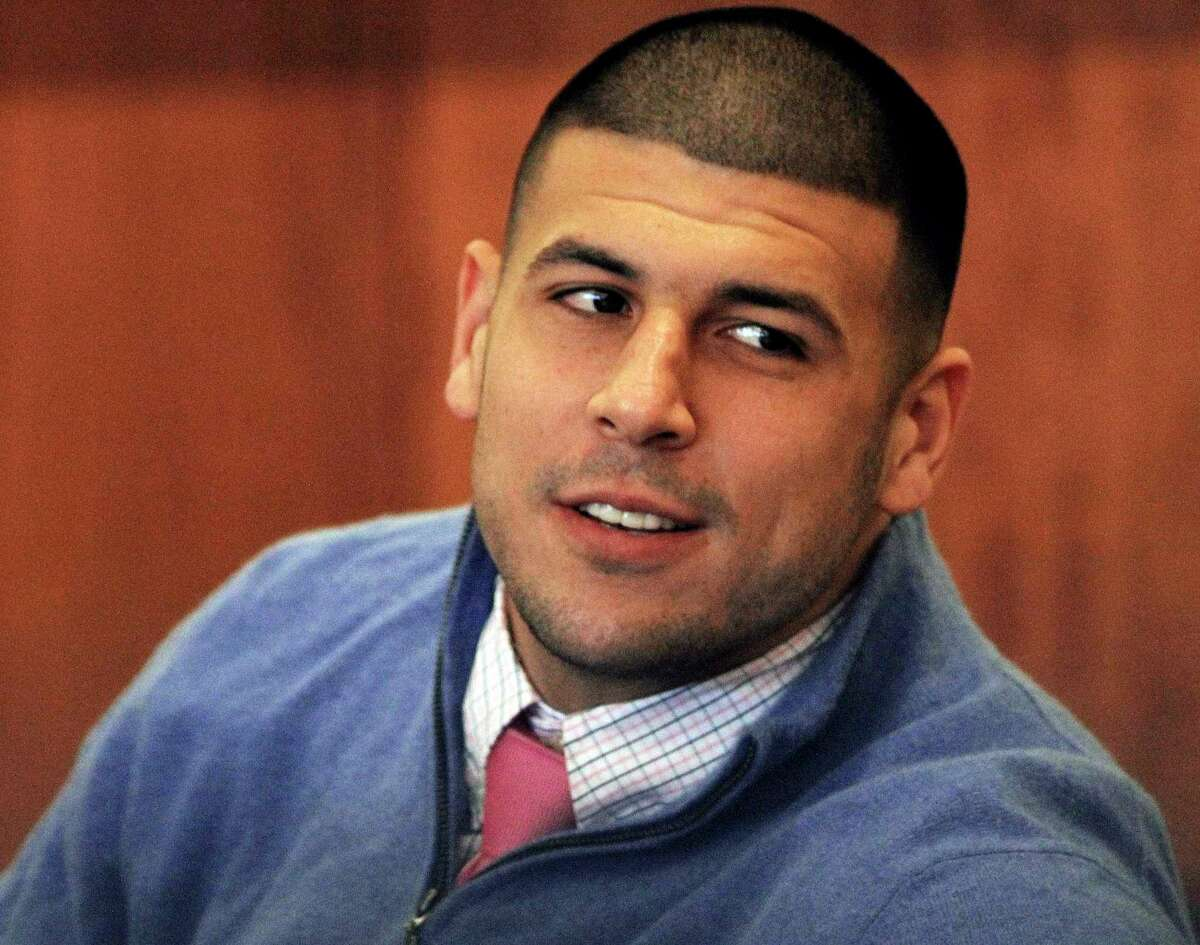 FILE - In this Oct. 1, 2014 file photo, former New England Patriots football player Aaron Hernandez looks back during an evidentiary hearing at Fall River Superior Court in Fall River, Mass. Authorities have returned to the home of ex-New England Patriots player Aaron Hernandez seeking sneakers they believe were worn on the night of a 2013 killing he's charged in. The Sun Chronicle reports state and local authorities went to Hernandez's North Attleborough home this week but seized no evidence. (AP Photo/The Boston Globe, Wendy Maeda, Pool)