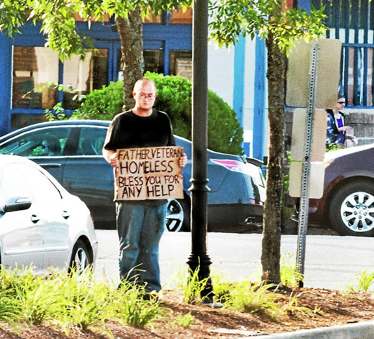 A man stands with a sign off the Post Road in Milford Friday