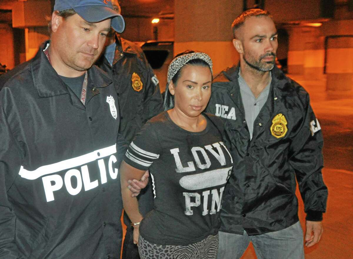 In this Monday, June 9, 2014 photo provided by the Drug Enforcement Administration, Samantha Barbash, center, is escorted by law enforcement officers following her arrest in New York. Barbash is allegedly part of a crew of New York City strippers who scammed wealthy men by drugging them and running up extravagant bills at topless clubs while they were in a daze, according to authorities. (AP Photo/DEA)