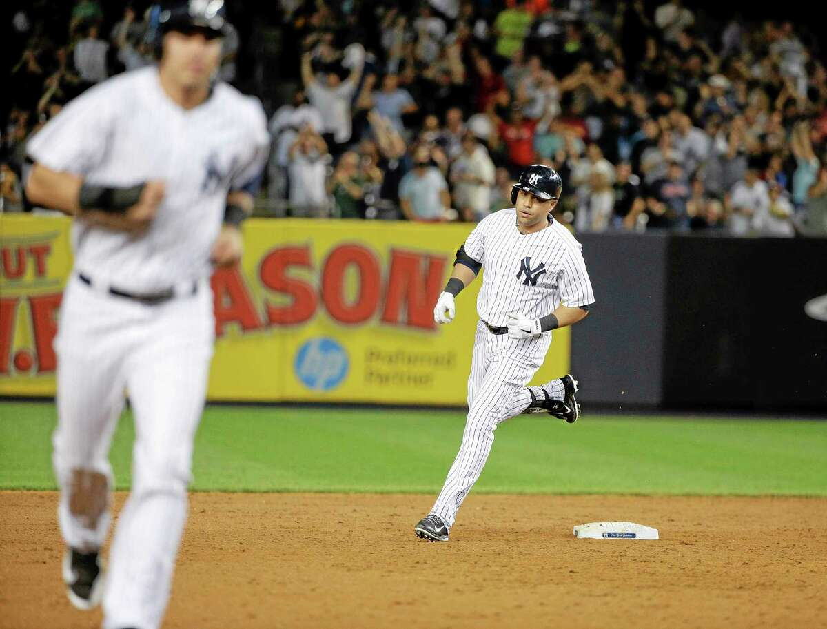 New York Yankees designated hitter Carlos Beltran, right, rounds the bases after hitting a grand slam home run against the Cleveland Indians in the sixth inning of a baseball game, Friday, Aug. 8, 2014, in New York. (AP Photo/Julie Jacobson)