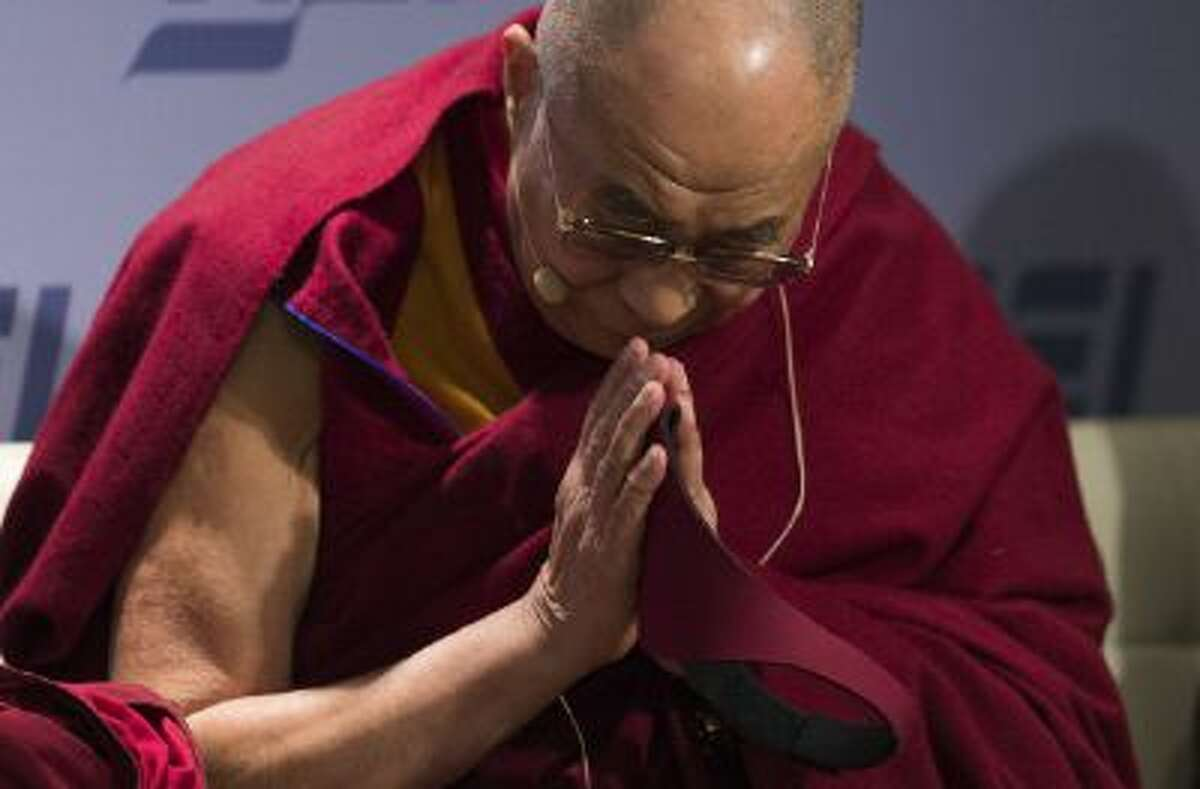 """The Dalai Lama prays as he arrives at the American Enterprise Institute (AEI) to hold a discussion on """"Happiness, Free Enterprise, and Human Flourishing"""" in Washington, DC, February 20, 2014. AFP PHOTO / Jim WATSON (Photo credit should read JIM WATSON/AFP/Getty Images)"""
