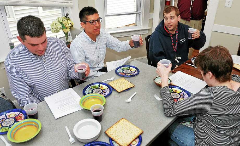 Sam Shwartz, a Chapel Haven special needs student, toasts as he hosts a Seder dinner at his New Haven home Monday. With him are friends Zachary Spielman, left, Matt Baker, right, and Lizzy Peck, bottom right. Photo: Peter Casolino — New Haven Register