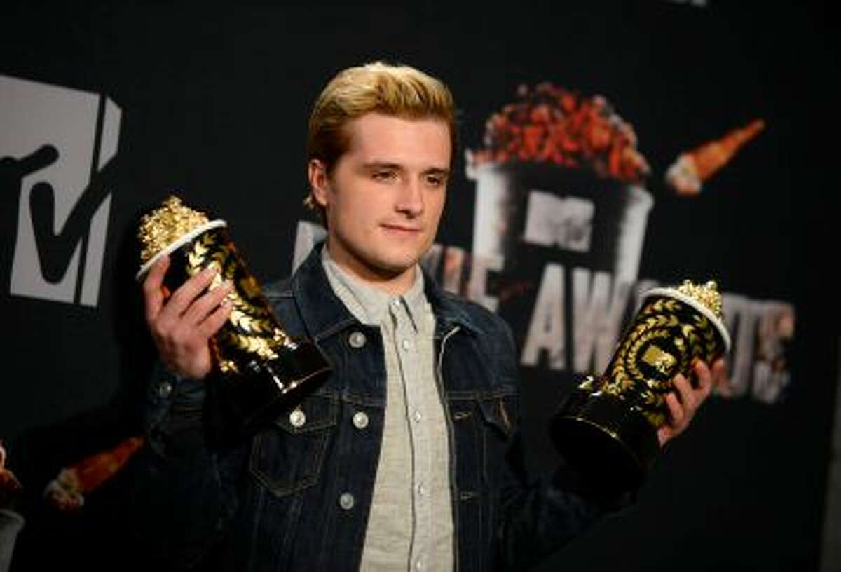 """Josh Hutcherson poses with his best male performance award and movie of the year award for """"The Hunger Games: Catching Fire"""" in the press room at the MTV Movie Awards on Sunday, April 13, 2014, at Nokia Theatre in Los Angeles. (Photo by Jordan Strauss/Invision/AP)"""