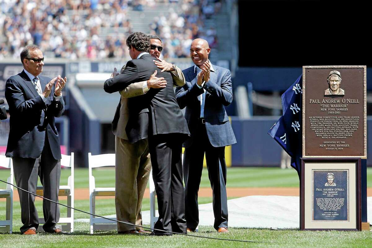 Former Yankee Paul O'Neill, center facing away, is congratulated by former manager Joe Torre, left, and former teammates Jorge Posada, embracing, and Mariano Rivera after unveiling a plaque, right, that will be displayed in Yankee Stadium's Monument Park.