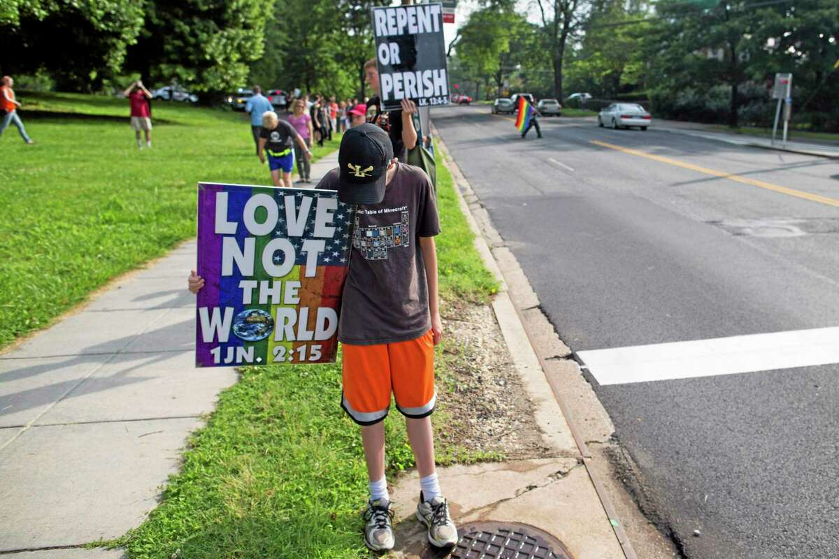 Demonstrator Gideon Hockenbarger of Topeka, Kansas holds a sign as members of the controversial Westboro Baptist Church protest outside Wilson High School in Washington, Monday, June 9, 2014. Hundreds of students, educators and community members turned out for a counter-protest against the anti-gay Westboro Baptist Church at a District of Columbia high school. Westboro targeted Wilson High School for a protest over the school's annual Pride Day event. About a dozen representatives of the Kansas-based church picketed near the school on Monday morning. (AP Photo/ Evan Vucci)