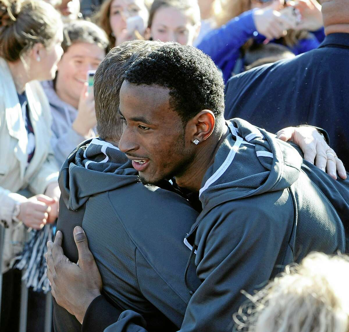 Connecticut men's basketball player DeAndre Daniels, right, hugs Connecticut women's head coach Geno Auriemma after Auriemma arrived on campus with his team for a rally celebrating their NCAA title on Wednesday, April 9, 2014, in Storrs, Conn. (AP Photo/Jessica Hill)