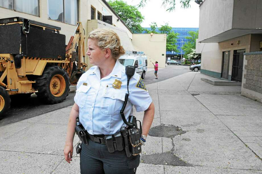 New Haven police Lt. Holly Wasilewski stands in an area of Church Street South, where commuters walk to and from the train station, seen behind her. Unfortunately, walkers who do that are trespassing. Photo: Mara Lavitt — New Haven Register     / Mara Lavitt