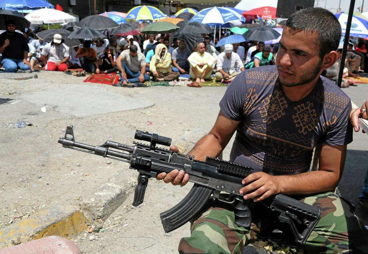 A Shiite fighter strands guard next to followers of Shiite cleric Muqtada al-Sadr attending open-air Friday prayers in the Shiite stronghold of Sadr City, Baghdad, Iraq, Friday, Aug. 8, 2014. (AP Photo/Karim Kadim)