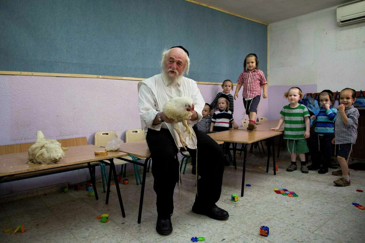 An ultra-Orthodox Jewish man holds a chicken as he talks to children Thursday about the Kaparot ritual in the city of Bnei Brak, near Tel Aviv, Israel. Observers believe the ritual transfers one's sins from the past year into the chicken, and the ritual is performed before the Day of Atonement, Yom Kippur, the holiest day in the Jewish year, which starts at sundown Friday.