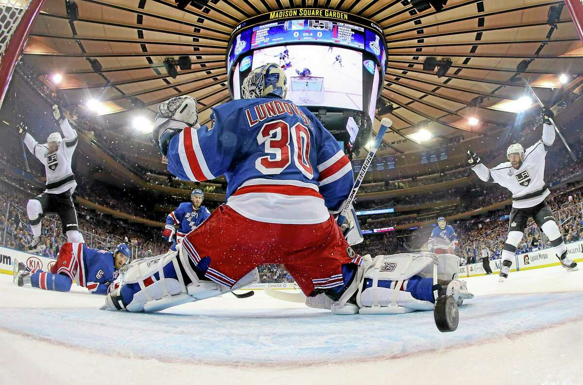 Los Angeles Kings center Jeff Carter (77), left, and left wing Dwight King (74), right, react as the puck bounces off the post and into the net past New York Rangers goalie Henrik Lundqvist (30) to end the first period of Game 3 of the Stanley Cup finals on Monday in New York.