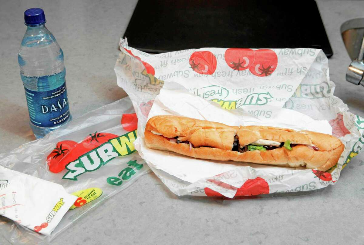 This 2009 photo shows a chicken breast sandwich and water from Subway on a kitchen counter in New York.