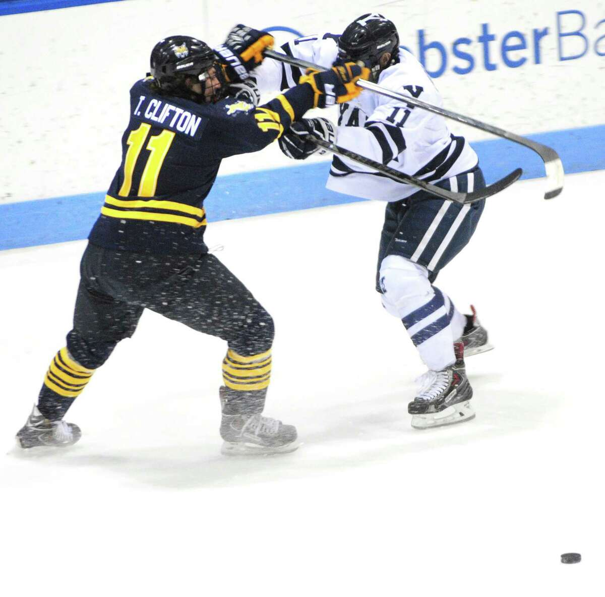 (Arnold Gold ó New Haven Register) Tim Clifton (left) of Quinnipiac and Trent Ruffolo of Yale fight for the puck in the first period at Ingalls Rink in New Haven on 2/14/2014.