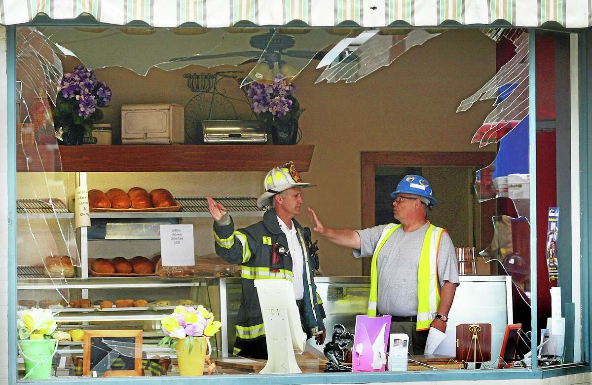 Emergency personnel investigate the damage at a bakery after an underground explosion Tuesday morning, June 10, 2014, on Main Street in Norwalk, Conn. The blast blew the windows out of the nearby bakery and knocked out power to the area.