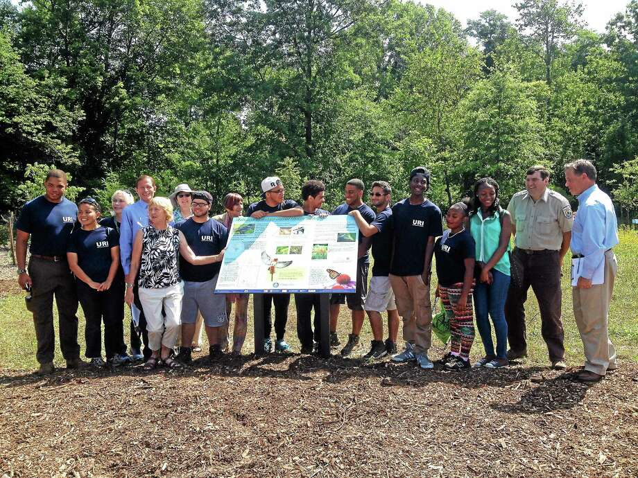 "Volunteers gather around a newly unveiled sign Friday at the Beaver Ponds Park, one of four ""urban oases"" in New Haven designated to provided habitat for migratory birds and other species. Photo: Kristin Stoller — New Haven Register"