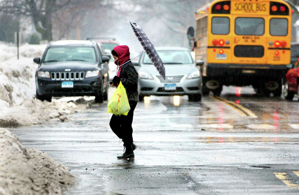 A woman loses her umbrella while crossing Center St. in West Haven on 2/19/2014.