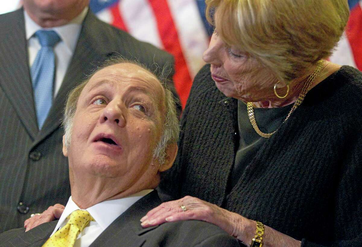 This March 30, 2011, file photo shows former White House press secretary James Brady, left, who was left paralyzed in the Reagan assassination attempt, looking at his wife Sarah Brady, during a news conference on Capitol Hill in Washington marking the 30th anniversary of the shooting. A Brady family spokeswoman says Brady has died at 73.