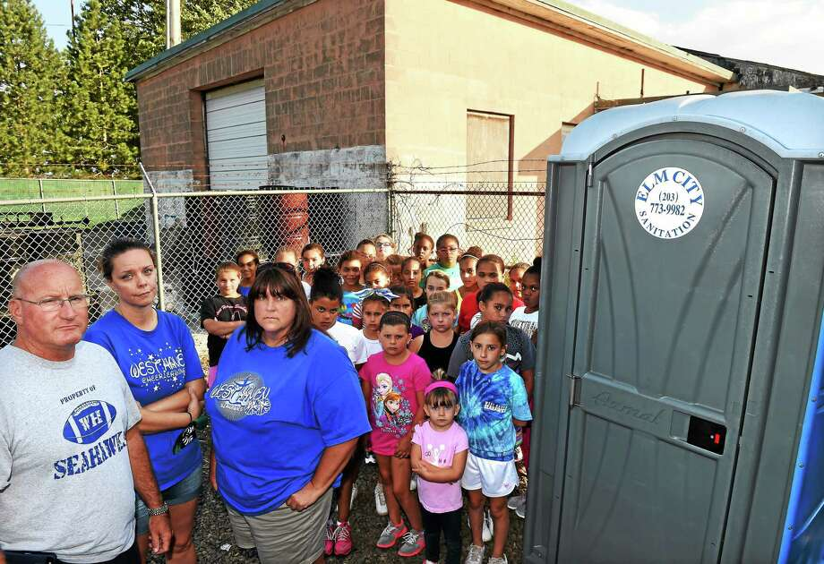 From left, Ray Tellier Midget Football League president Mike Last, parent and fundraiser Bridgette Hoskie, and cheer coordinator Cebi Waterfield with cheerleaders that really, really want a true bathroom in the building behind them instead of porta-potties. Photo: Mara Lavitt — New Haven Register    / Mara Lavitt