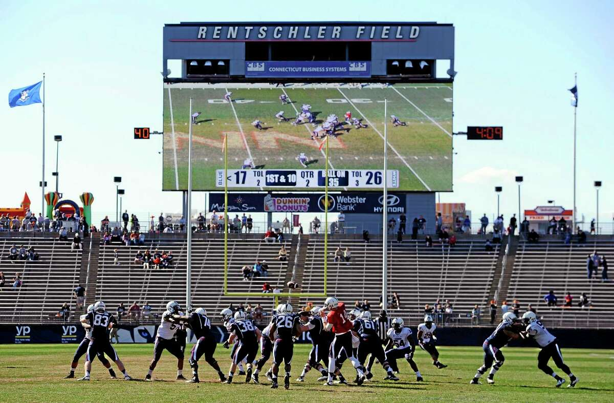 In this April 12, 2014 file photo Connecticut players run a play during the first half of UConn's Blue-White spring NCAA college football game at Rentschler Field, in East Hartford, Conn. Construction is nearly complete for UConn's new basketball training center in July 2014. In a series of projects designed to keep the schoolís athletic programs nationally competitive, the university has committed to building an on-campus hockey arena, and plans new facilities for soccer, baseball and softball. But athletic Director Warde Manuel said enlarging the 40,000-seat football stadium wonít make sense until the school can sell the existing seats. (AP Photo/Jessica Hill, File)