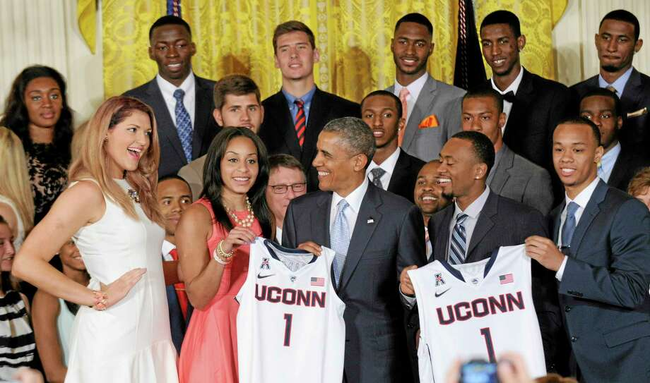 Stefanie Dolson, left, smiles at President Barack Obama during an event to welcome the NCAA champion men's and women's basketball teams to the East Room of the White House in Washington on Monday. Other team members presenting Obama with a jersey are Bria Hartley, Ryan Boatright, and Shabazz Napier. Photo: Susan Walsh — The Associated Press   / AP