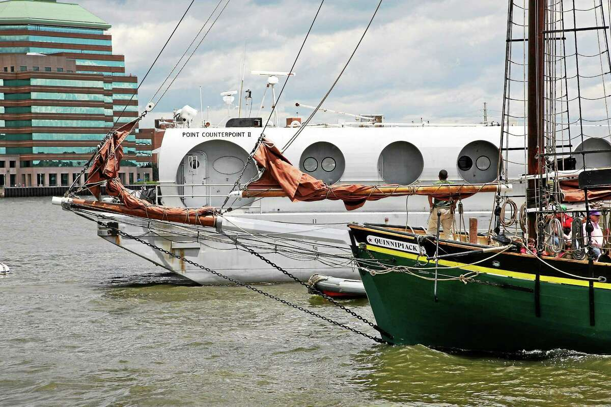 File photo: The Quinnipiack schooner passes the Point Counterpoint concert barge, which has been docked at the Long Wharf Pier for the past year.