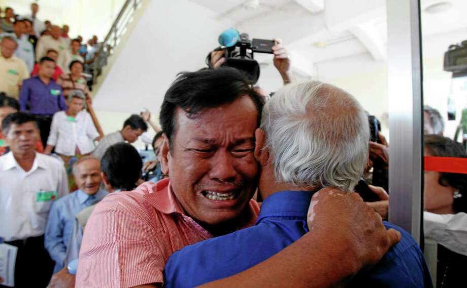 Cambodian former Khmer Rouge survivors, Soum Rithy, left, and Chum Mey, right, embrace each other after the verdicts were announced, at the U.N.-backed war crimes tribunal in Phnom Penh, Cambodia, Thursday, Aug. 7, 2014. Three and a half decades after the genocidal rule of Cambodia's Khmer Rouge ended, the tribunal on Thursday sentenced two top leaders of the former regime to life in prison on war crimes charges for their roles during the country's 1970s terror. (AP Photo/Heng Sinith) Photo: AP / AP