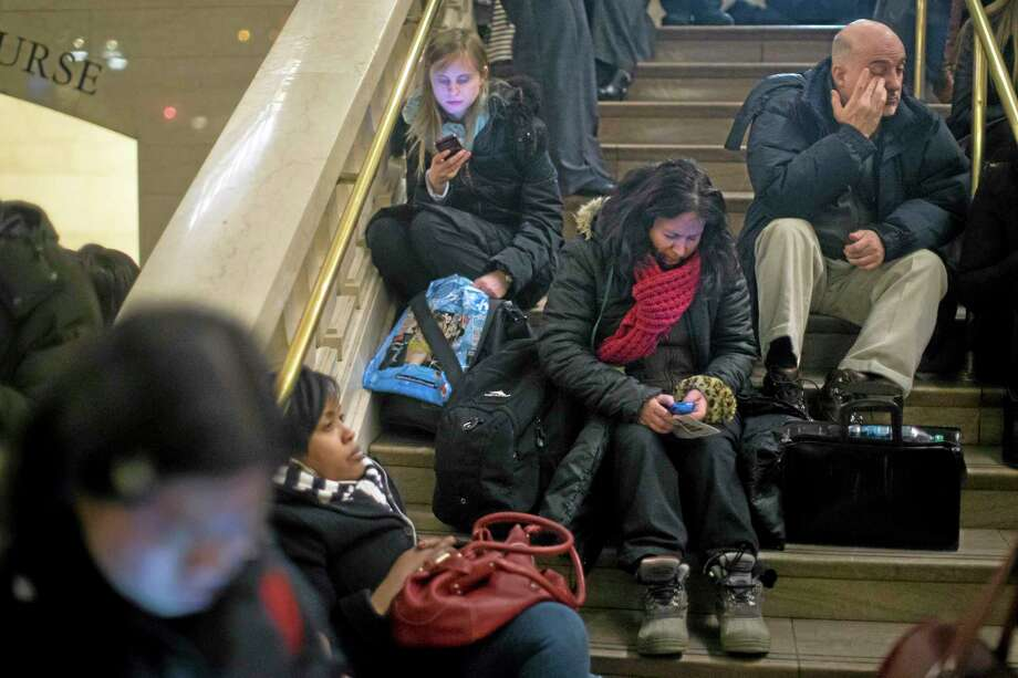Commuters rest on the stairs of the main hall of Grand Central Terminal after a power problem with Metro-North Railroad's computer system caused the suspension of service on the Hudson, Harlem, and New Haven lines Jan. 23. Photo: John Minchillo — The Associated Press   / FR170537 AP