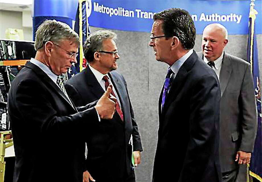 Connecticut Transportation Commissioner James Redeker, left, gives Connecticut Gov. Dannel Malloy, foreground right, two thumbs up after a news conference at MTA headquarters, in New York June 9, 2014. Metro-North president Joseph Giulietti, is second left, and  MTA Chairman and CEO Thomas Prendergast is at right. (AP Photo/Richard Drew) Photo: AP / AP