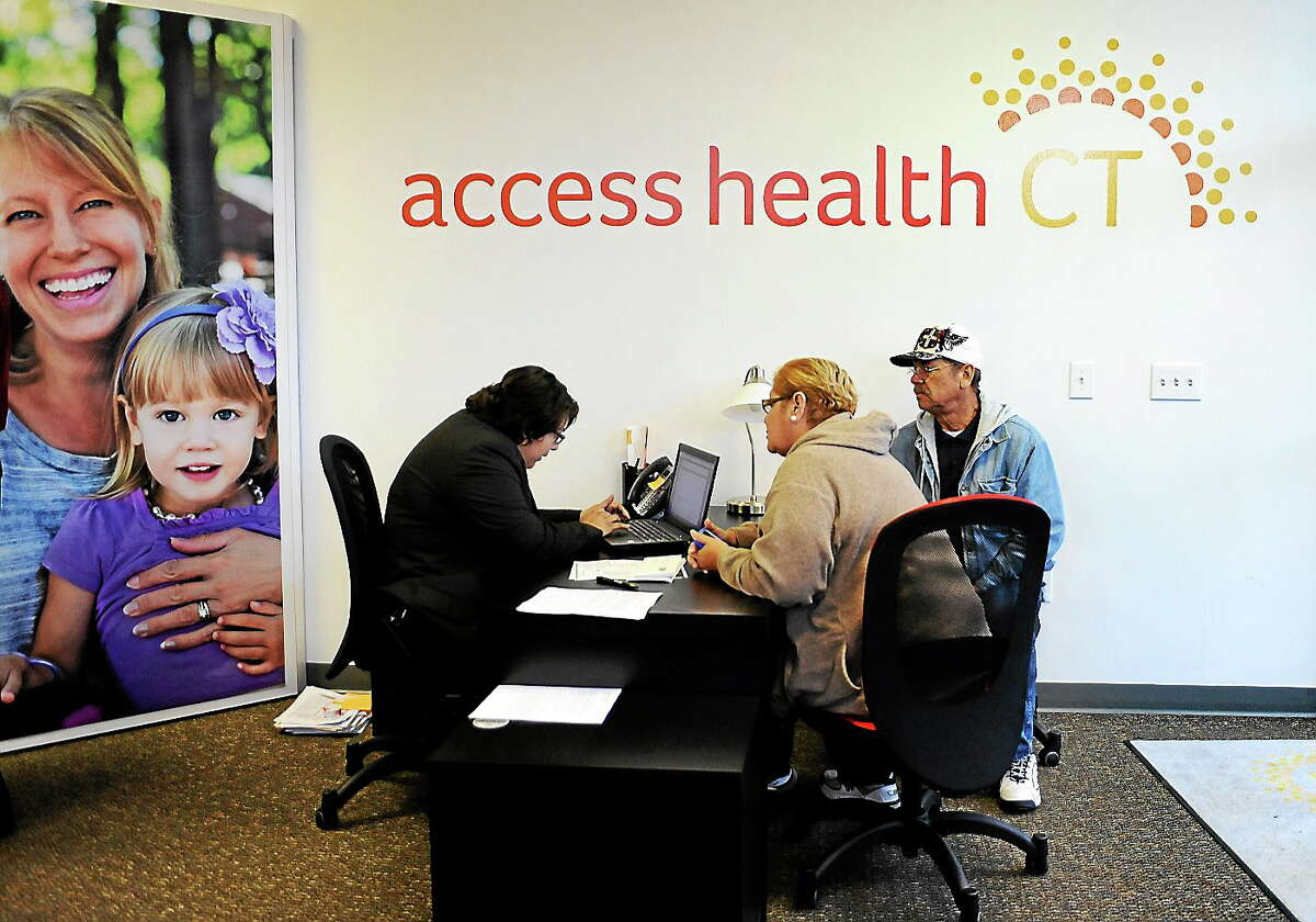 Gildred Ortiz, center and Julio Colon, right, receive help from outreach worker for Access Health CT, Cristela Solorio Ruiz during a grand opening for Connecticut's health insurance exchange's first insurance store on Nov. 7, 2013 in New Britain, Conn.