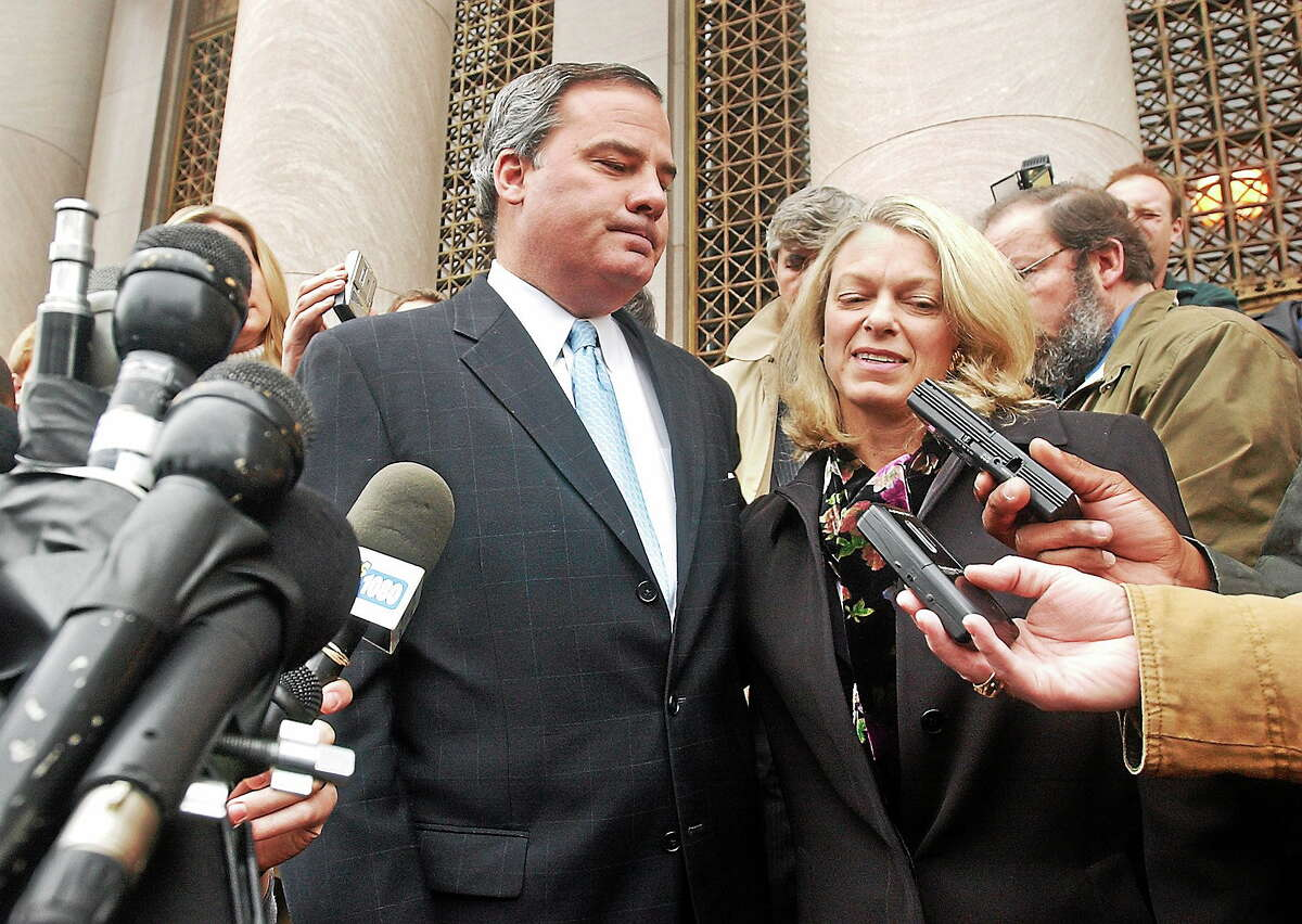 Former Gov. John G. Rowland speaks with members of the press outside court after pleading guilty to the federal charge of conspiracy to steal honest services Dec. 23. 2004. At right is his wife, PatriciaD.