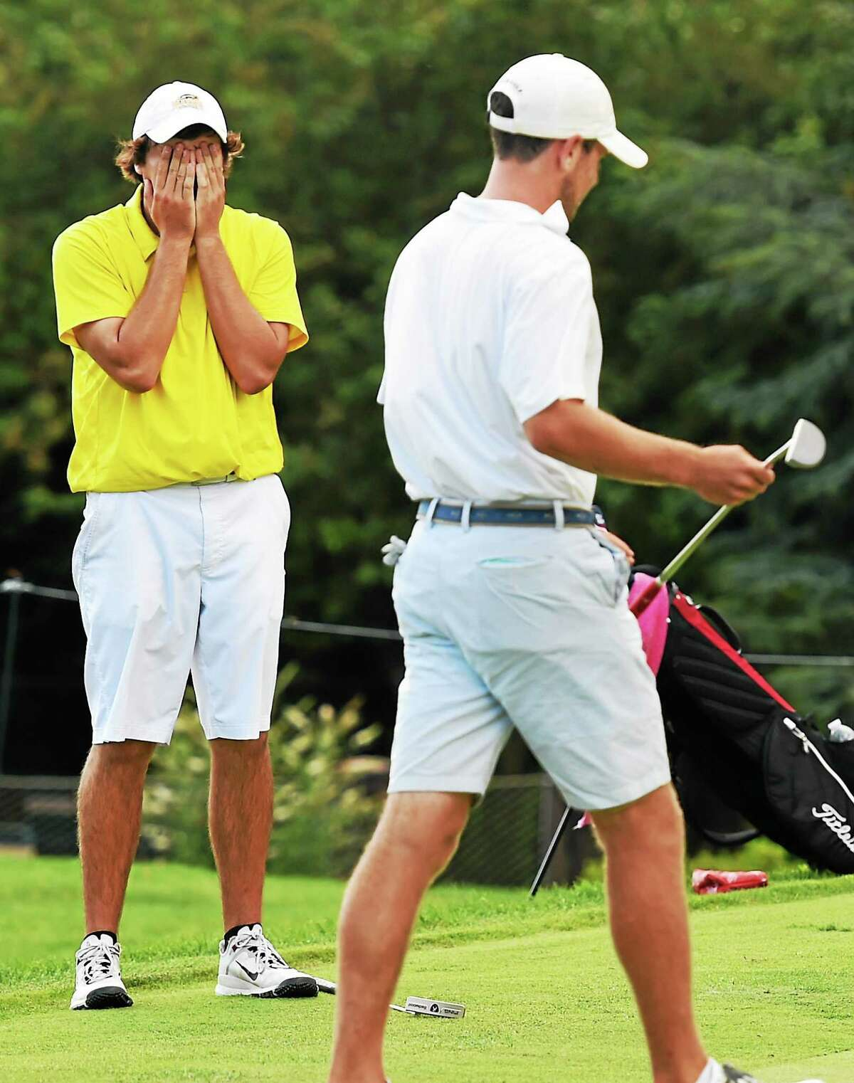 Brock Kovac, left, reacts to putting problems on the 18th green as Will Bernstein prepares to play in the 13th Northern Junior Championship.