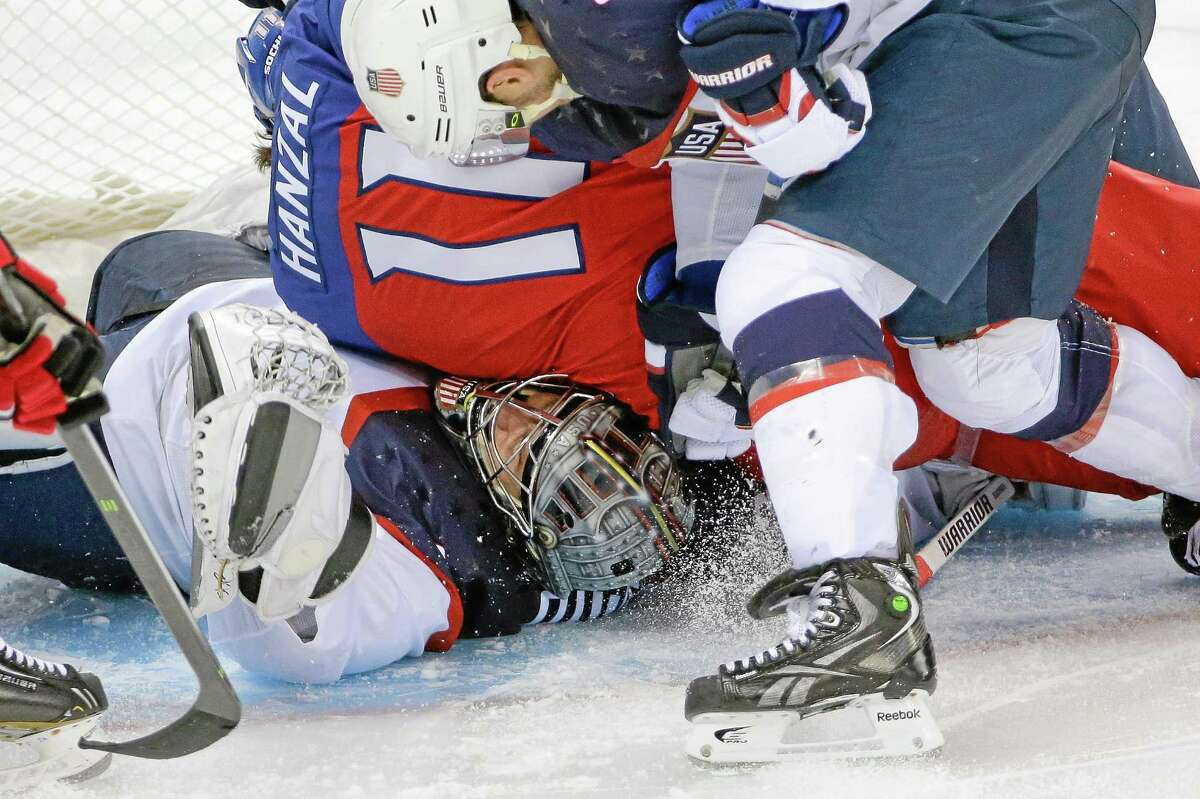 USA goaltender Jonathan Quick of Hamden is crushed under Czech Republic forward Martin Hanzal during the third period of the United States' 5-2 win over the Czech Republic in Shayba Arena on Wednesday at the Winter Olympics in Sochi, Russia.