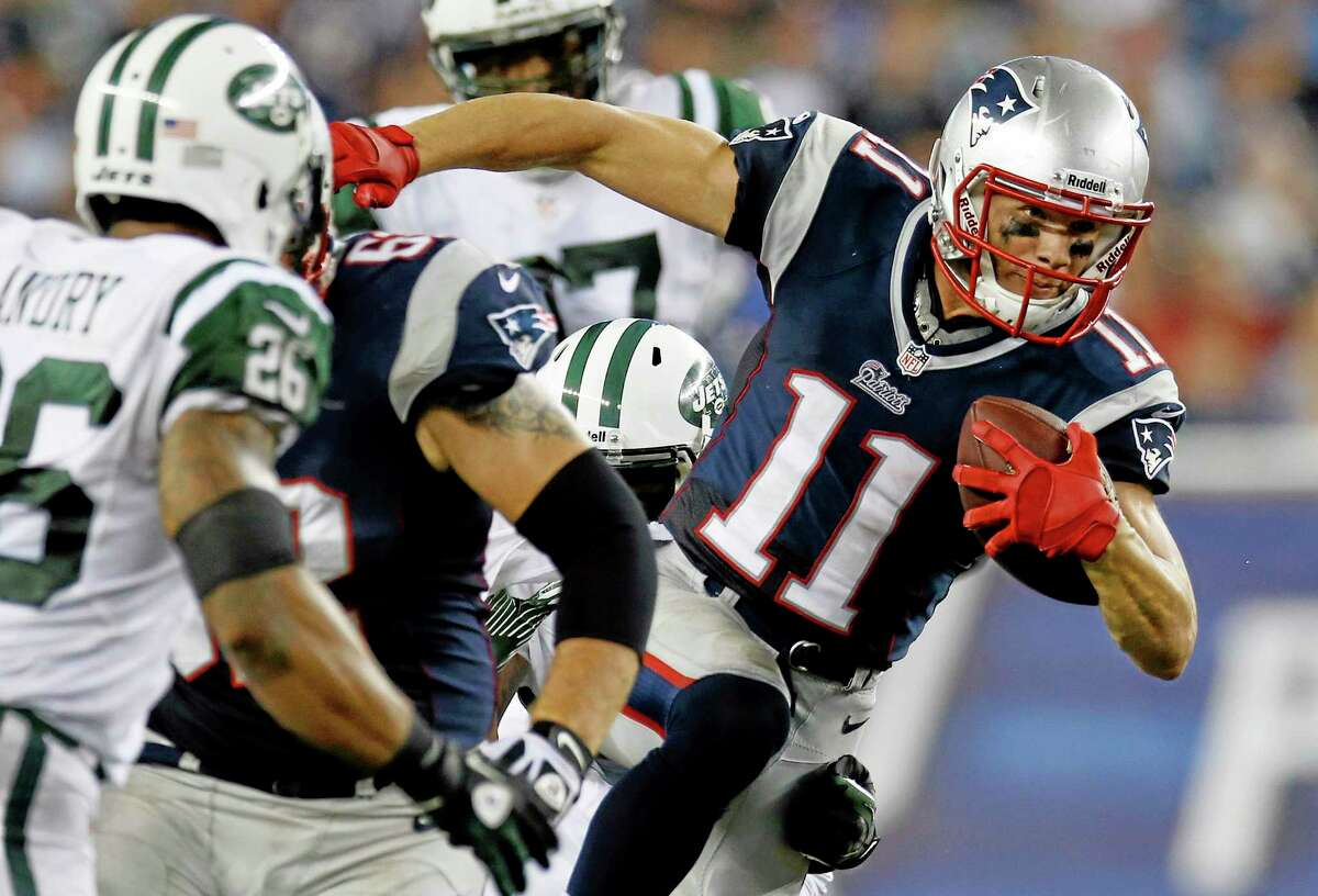 In this Sept. 13, 2013 file photo, New England Patriots receiver Julian Edelman runs past New York Jets safety Dawan Landry during the second quarter of a game in Foxborough, Massachusetts. Edelman surprisingly emerged as the Patriots top receiver last season, and he says he won't change just because he signed a big contract in the offseason.
