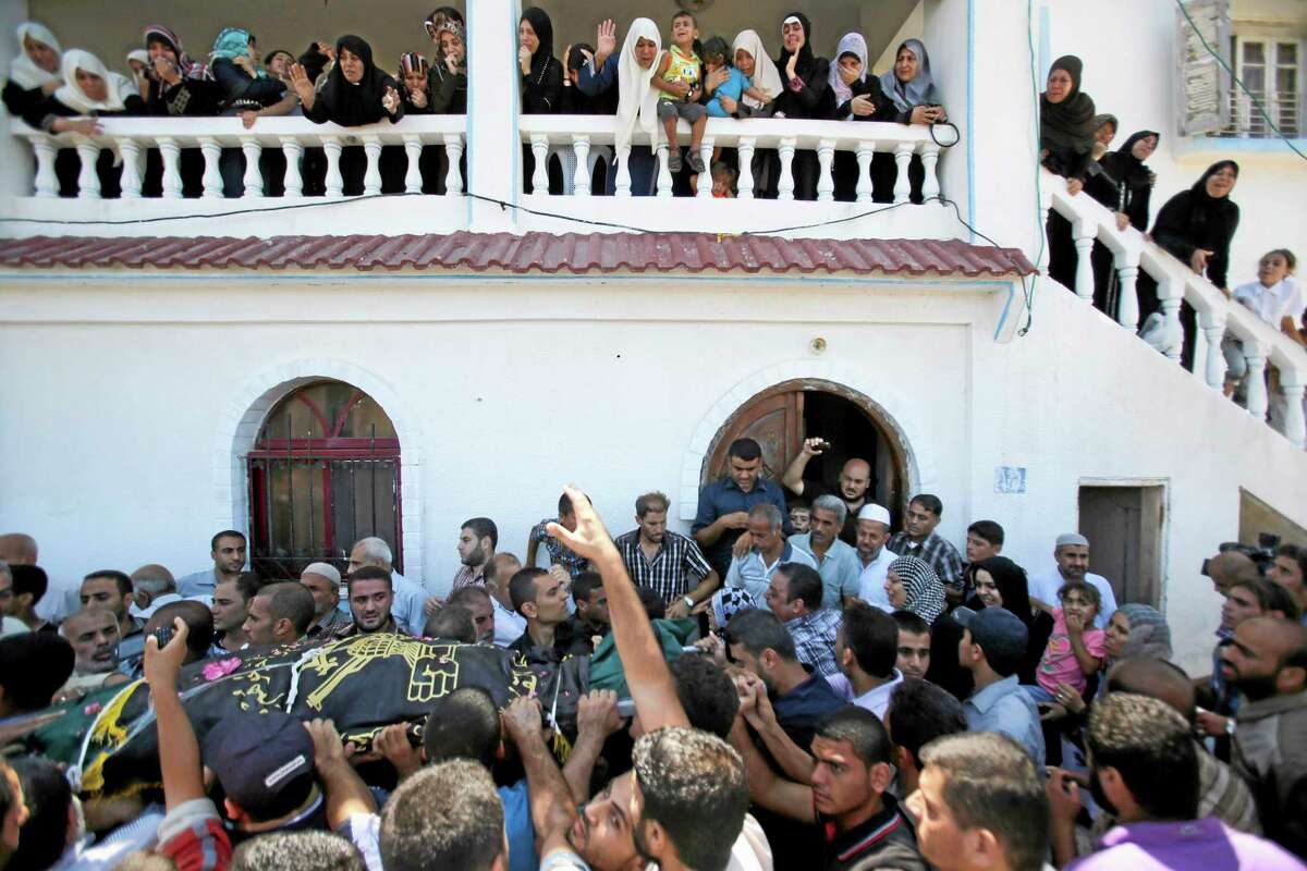 Palestinians carry the body of Islamic Jihad militant Shaaban Al-Dahdouh, which was found under the rubble yesterday, during funeral in Gaza City, Wednesday, Aug. 6, 2014. (AP Photo/Hatem Moussa)