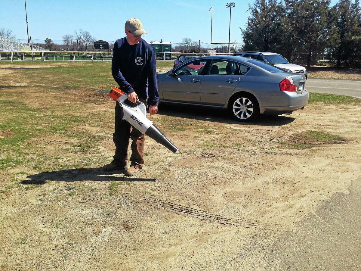 Facilities employee Jared Twomey with battery-powered blower. Register photo — Sean Carlin