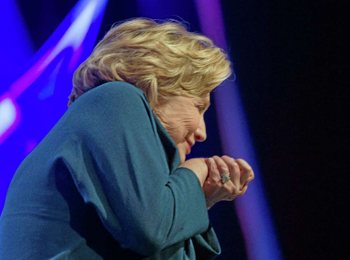 Former U.S. Secretary of State Hillary Rodham Clinton ducks as an object is thrown on stage during an address to members of the Institute of Scrap Recycling Industries during their annual convention at the Mandalay Bay Convention Center, Thursday, April 10, 2014, in Las Vegas. Clinton, a possible presidential contender in 2016, ducked but did not appear to be hit by the object, and then joked about the incident. Security ushered out a woman who said she threw a shoe but didn't identify herself to reporters or explain the action. (AP Photo/Las Vegas Sun, Steve Marcus) LAS VEGAS REVIEW-JOURNAL OUT