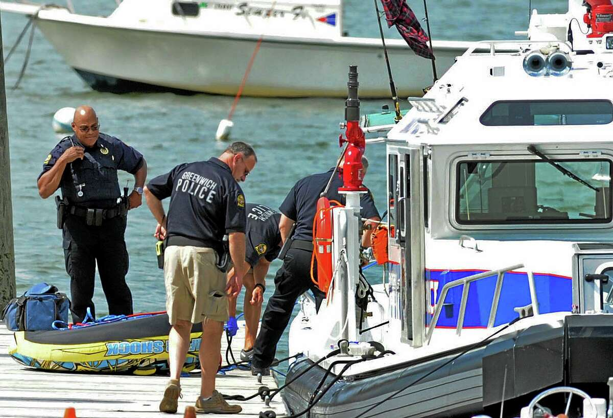 Police work at the scene of a boating accident near the Old Greenwich Yacht Club at Greenwich Point, Conn., Wednesday afternoon, Aug. 6, 2014. The Greenwich harbormaster said one girl was killed and another was injured. The accident involved two young women operating a boat and two others being towed in a tube. He said those in the tube flipped out and were hit by the boat. (AP Photo/Greenwich Time, Bob Luckey) MANDATORY CREDIT