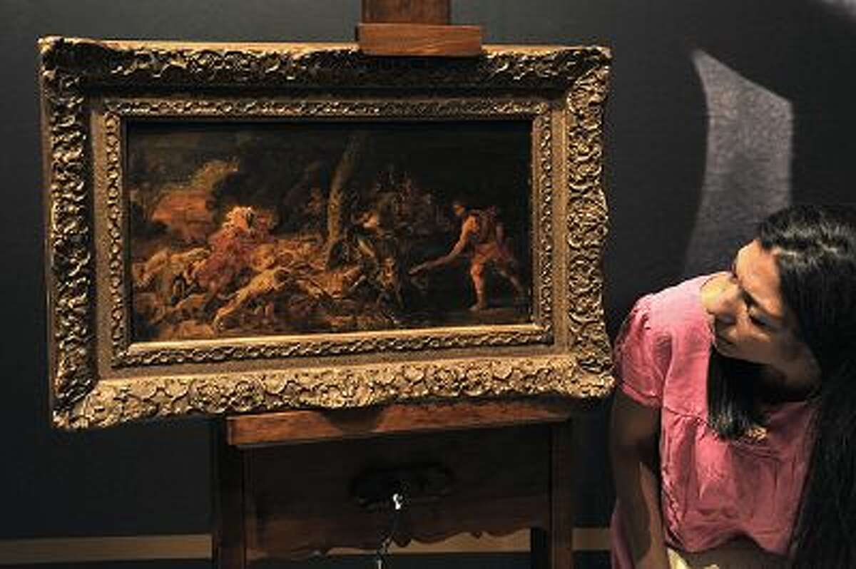 """An employee presents the stolen 17th-century oil sketch """"The Calydonian Boar Hunt"""" attributed to the Flemish master, Peter Paul Rubens' workshop, during its presentation at the national gallery in Athens on September 8, 2011. The painting was snatched in 2001 from the Fine Arts Museum of Ghent in Belgium and recovered in Greece a week ago during an police operation. AFP PHOTO / LOUISA GOULIAMAKI (Photo credit should read LOUISA GOULIAMAKI/AFP/Getty Images)"""
