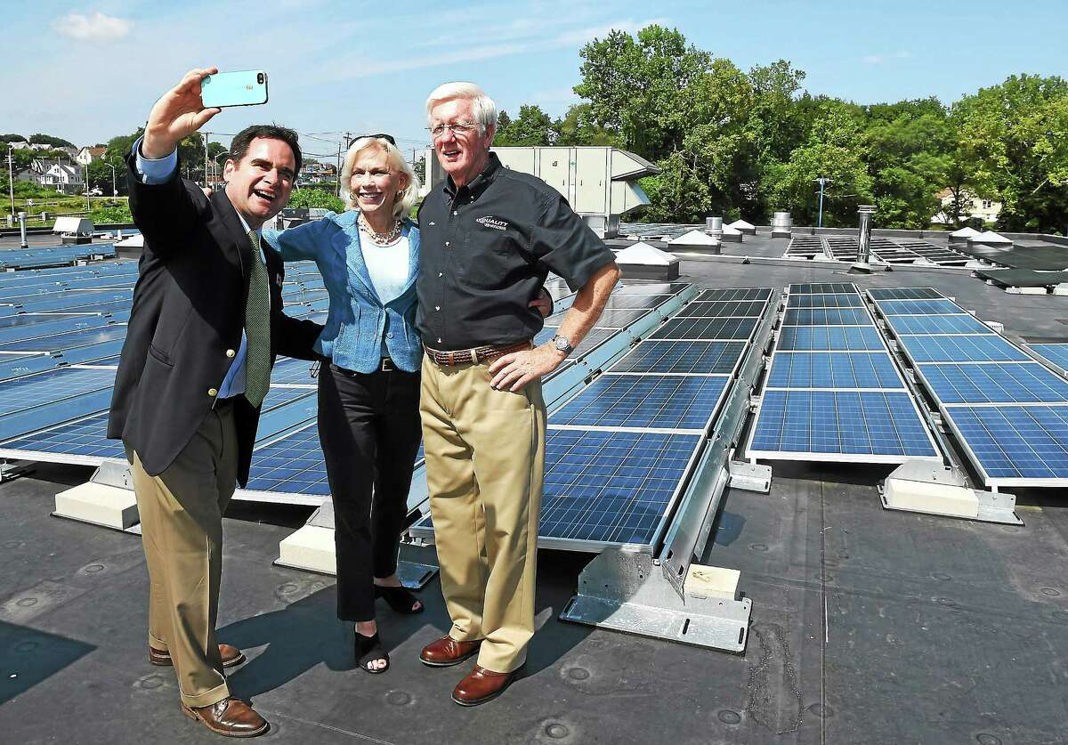 State Department of Energy and Environmental Protection Commissioner Rob Klee takes a selfie with state Rep. Lonnie Reed of Branford, co-chairwoman of the legislature's energy and technology committee, and Quality Hyundai owner Joe Blichfeldt Sr. in front of the new soalr array on the roof of the business Wednesday.