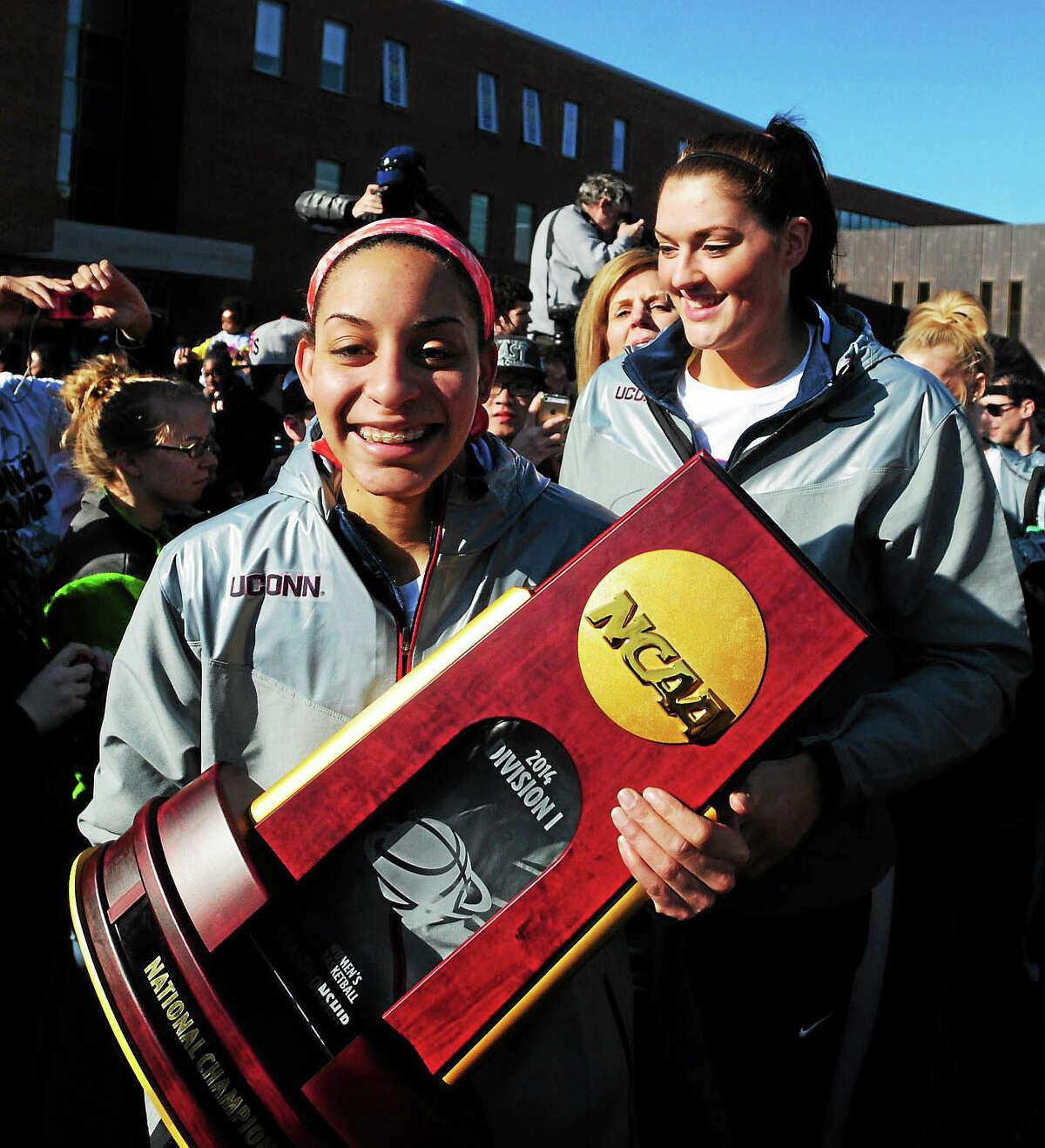 UConn guard Bria Hartley, left, carries the NCAA women's national championship trophy at the victory rally at Storrs. Stefanie Dolson is behind her. Peter Hvizdak - New Haven Register