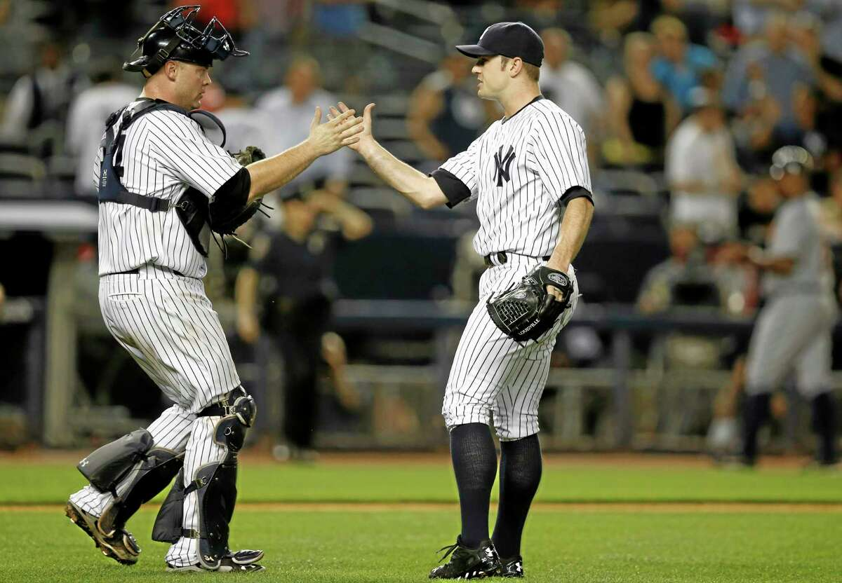 New York Yankees catcher Brian McCann, left, congratulates the Yankees relief pitcher David Robertson after Robertson closed out the Yankees 2-1 victor over the Detroit Tigers in a baseball game at Yankee Stadium in New York, Monday, Aug. 4, 2014. (AP Photo/Kathy Willens)