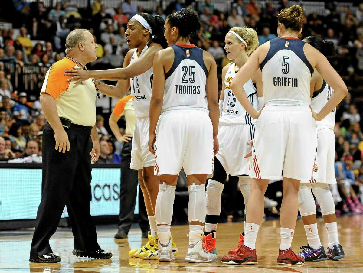 The Connecticut Sun's Kelsey Bone, holds back official Tom Mauer as he has a word with the Sun's Katie Douglas, center, during the second half of an 82-66 loss to the Sky.