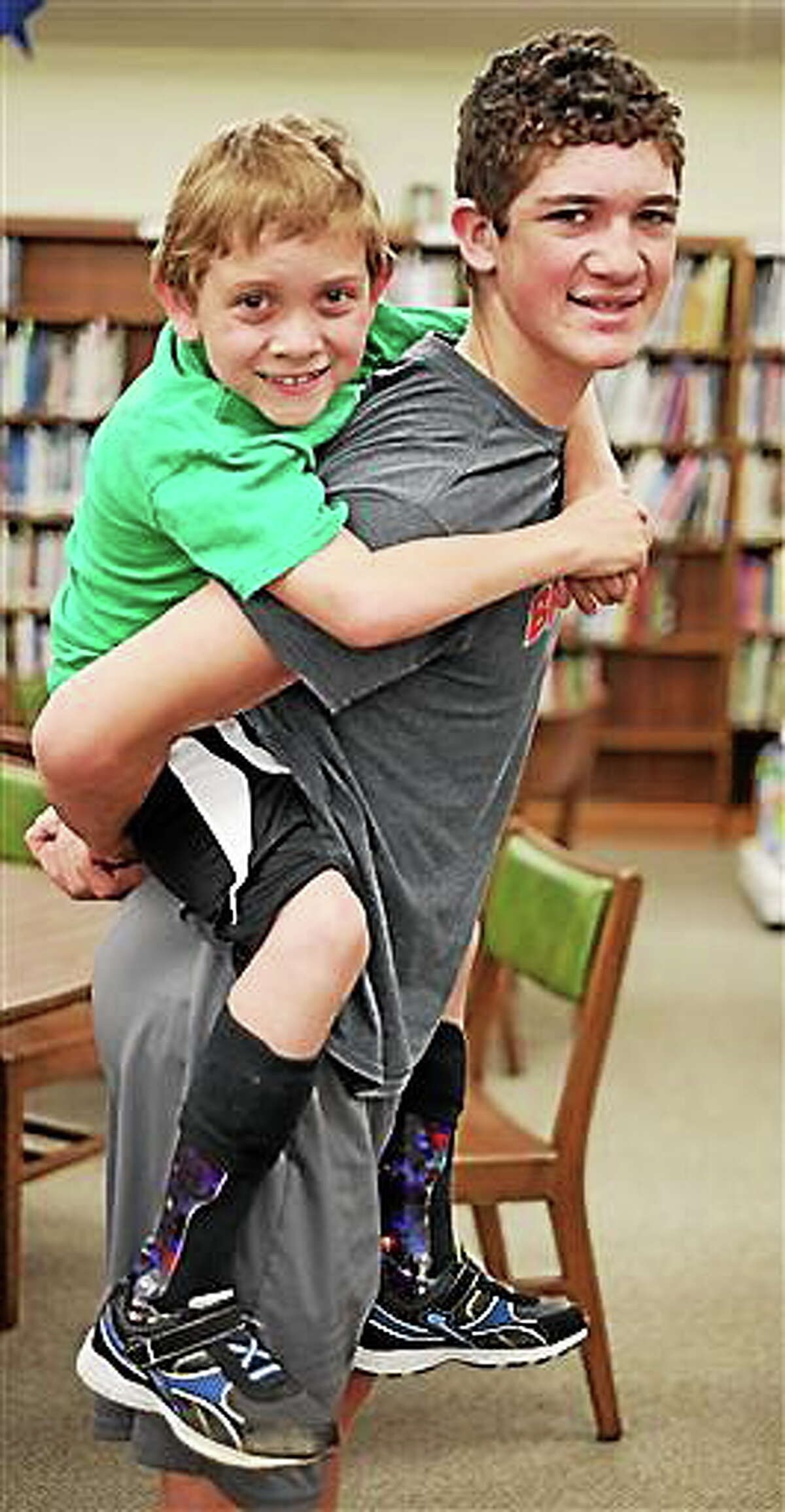 Hunter Gandee, 14, and his brother Braden Gandee, 7, Thursday, May 8, 2014, at Bedford Junior High School in Bedford, Mich. The two will be making a walk to Ann Arbor in June to raise awareness for muscular dystrophy, which afflicts Braden.