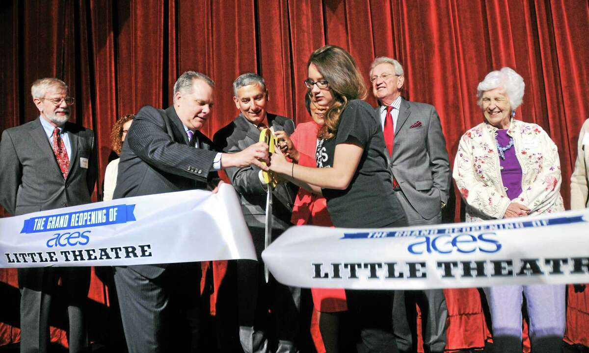 From left, ACES Executive Director Craig Edmonson, state Sen. Len Fasano, New Haven Mayor Toni Harp (partially hidden) and Lexi Fonda of the ACES Vocal Ensemble cut a ribbon symbolically reopening The Little Theater in New Haven last week.